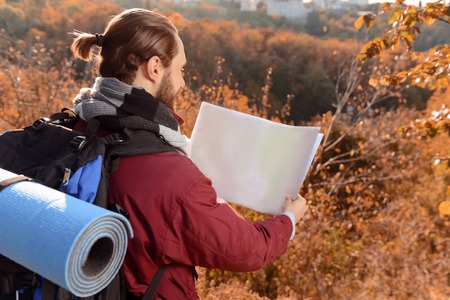 upbeat: Upbeat agreeable bearded guy holding map and standing half turned while traveling
