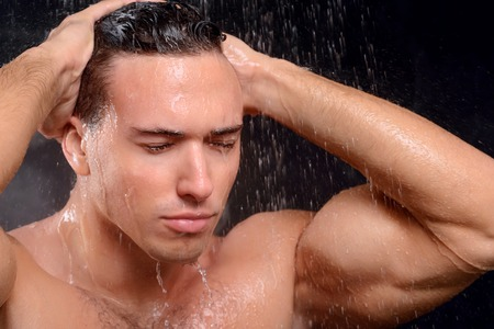 taking shower: Get the energy. Close up of sexually attractive handsome man taking shower and feeling glad