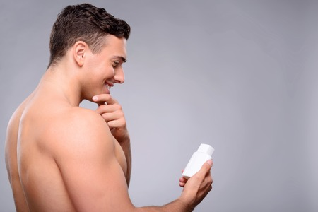 bloke: Content agreeable smiling gut holding lotion and keeping hand on his chin while feeling happy