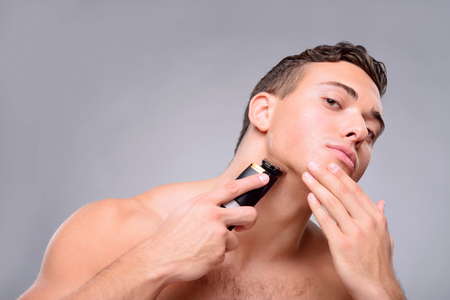 laugher: Positive handsome young man holding shaving machine and using it while taking care of himself