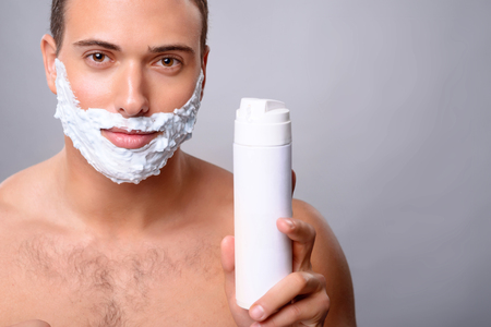 lather: Pleasant handsome upbeat man holding shaving lather and going to shave while feeling confident