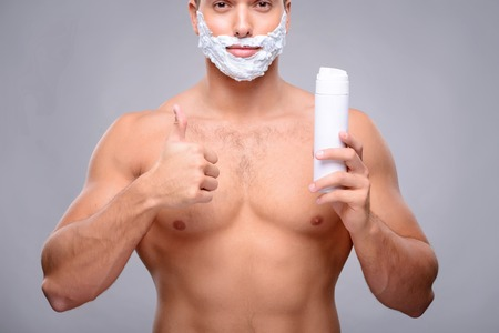 sexually: Agreeable handsome sexually attractive man holding shaving lather and going to shave while thumbing up