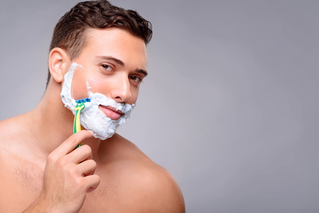 feeling up: Close up of pleasant handsome upbeat guy holding razor and shaving while feeling content Stock Photo