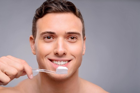 bloke: Pleasant smiling handsome guy holding toothbrush and going to clean teeth while evincing joy