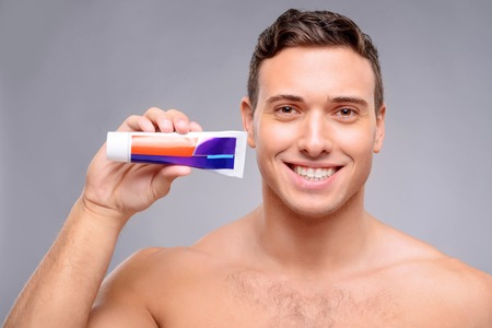 tooth paste: Pleasant delighted handsome guy holding tooth paste and expressing gladness