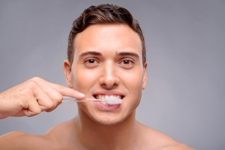 bloke: Cheerful content handsome guy holding brush while cleaning teeth Stock Photo