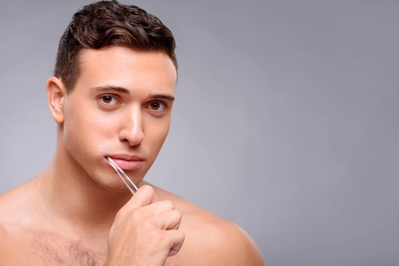 bloke: Pleasant content positive guy holding tooth brush and cleaning teeth while feeling glad