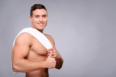 bloke: Life is great. Pleasant handsome positive guy holding towel on the shoulder and thumbing up after getting shower