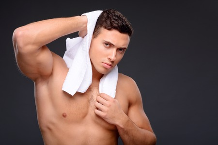sexually: Pleasant sexually attractive man holding towel on the shoulders after taking a shower Stock Photo
