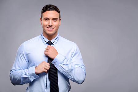 bloke: Pleasant cheerful handsome man wearing tie and feeling delighted while going to work Stock Photo