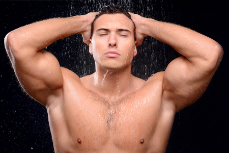shower man: Content handsome man closing his eyes and taking shower while feeling delighted