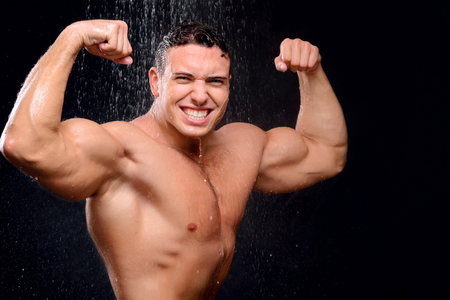 agreeable: Agreeable handsome man smiling and taking shower while felling content