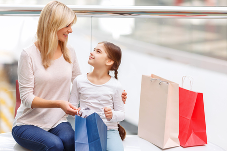 elated: Cheerful elated mother and daughter sitting on the bench and holding packages while resting after shopping Stock Photo