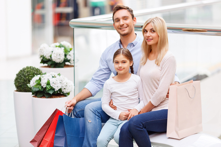 elated: Pleasant elated young family sitting on the bench and holding packages while bonding to each other Stock Photo