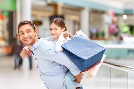 agreeable: Pleasant joyful agreeable father holding his daughter on the back and having fun while making shopping