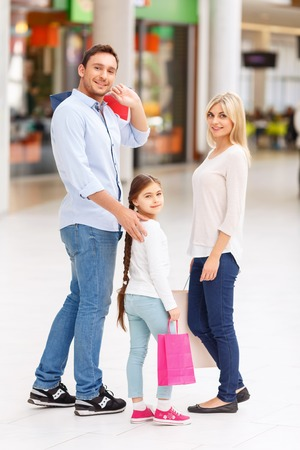 pleasant: Pleasant parents with their daughter holding packages and walking around mall while  having shopping