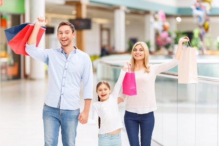 agreeable: Pleasant overjoyed agreeable family holding their hands up and having shopping while walking around the mall
