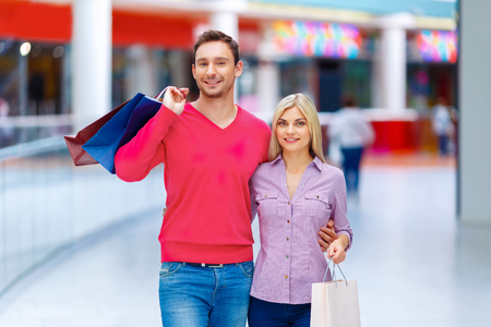 affinity: Young family. Pleasant content blissful couple bonding to each other and holding packages while having shopping in  a mall