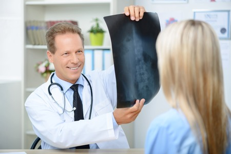 elated: Pleasant professional elated doctor holding radiograph and showing it to his patient while feeling content