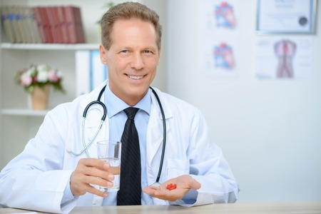 doctor giving glass: Pleasant cheerful content doctor holding glass of water and giving pills to his patient while being involved in work Stock Photo
