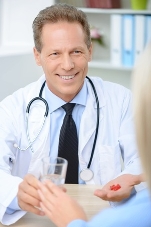 doctor giving glass: Vivacious smiling professional doctor holding glass of water and pills giving them to his patient.