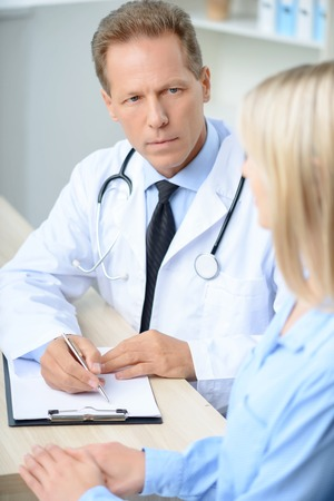 agreeable: Serious agreeable professional doctor sitting at the table and listening to his patient while being involved in work Stock Photo