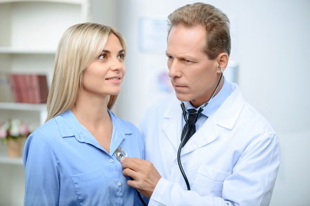 agreeable: Agreeable professional doctor holding stethoscope and examining his patient Stock Photo