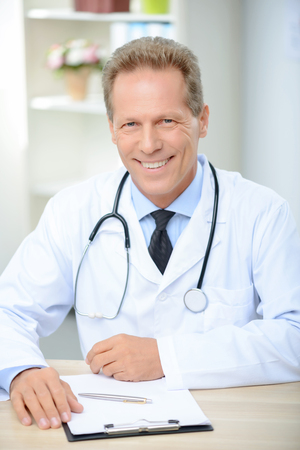 elated: Pleasant cheerful elated doctor sitting at the table and smiling while being involved in work Stock Photo