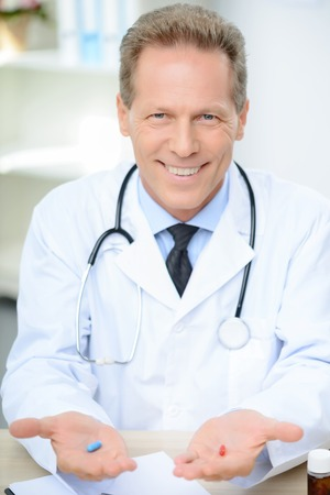 agreeable: Agreeable smiling doctor sitting at the table and holding pills while being involved in work Stock Photo