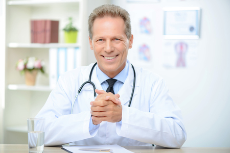 agreeable: Agreeable smiling positive doctor sitting at the table and holding hands together while being busy at work