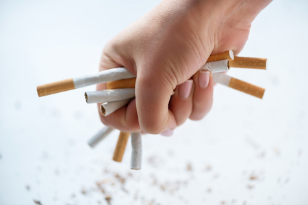 Close up of bunch of cigarettes in hands of young girl holding it while standing on white background Stock Photo