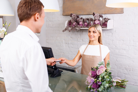 appealing: Upbeat appealing young florist holding credit card and talking with client while serving him Stock Photo