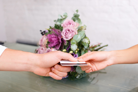 relaxed business man: Close up of credit card in hand of client giving it to professional florist while buying flowers