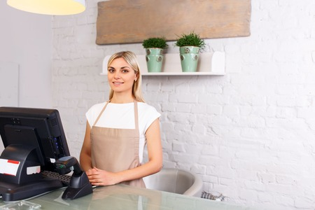 elated: Nice professional elated florist smiling and standing st the counter while doing hr job Stock Photo