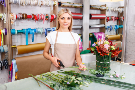 secateur: Pleasant vivacious professional florist holding secateurs and cutting the flowers while doing her job