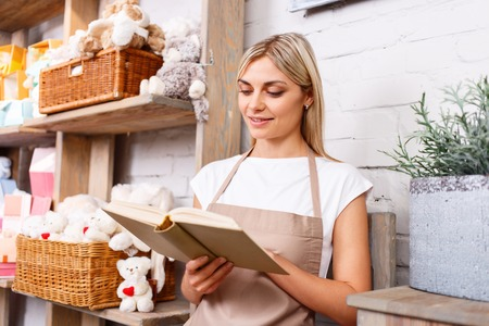 agreeable: Agreeable charming peaceful florist holding book and reading it while resting at work