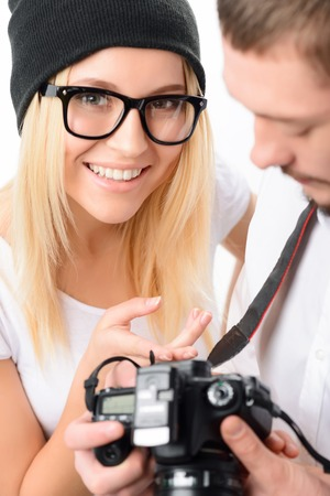 prototypical: Young attractive model with male photographer smiles brightly while looking through the taken frames. Stock Photo