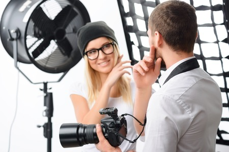 prototypical: Young male photographer talks with female model about important photoshoot issues Stock Photo