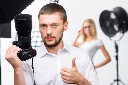 prototypical: Nice-looking young male photographer holds up a camera while showing thumbs up