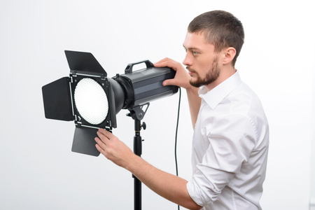 goodlooking: Young good-looking male photographer is busy fixing the spotlight.