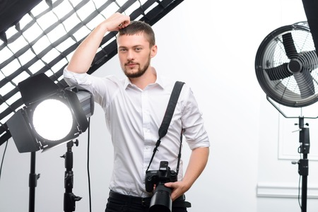 appealing: Young appealing professional photographer leans on the spotlight while supporting his camera