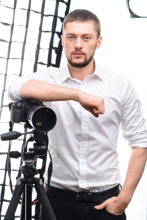 male: Young male attractive photographer is posing with his tripod and camera.