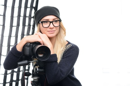 appealing: Young appealing female model leans on tripod camera while sitting