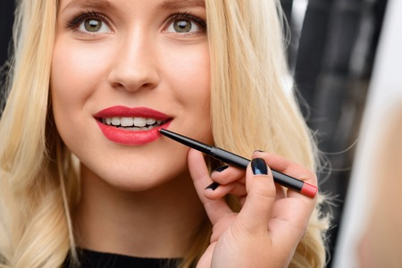 Female nice-looking model waits while red lipstick is being applied by makeup artist.