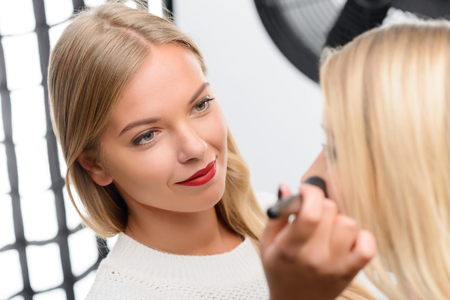Female makeup artist looks trusting when smiles during her accurate work. Stock Photo