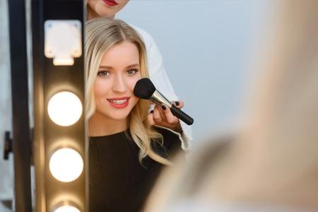 메이크업 아티스트가 그녀와 함께 작동하는 동안 여성 젊은 모델은 조명 거울 앞에 앉아있다. 스톡 콘텐츠