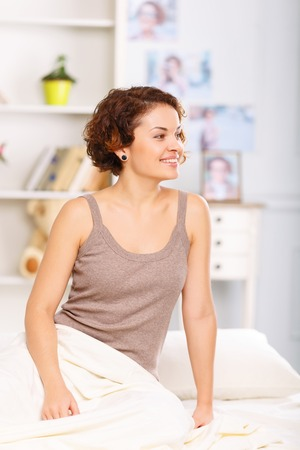 agreeable: Share energy with me. Agreeable pleasant young woman sitting in bed and looking aside Stock Photo