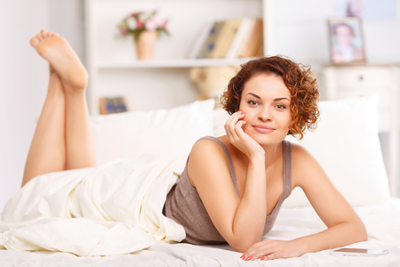 upbeat: Pretty charming upbeat girl holding hand near her face and lying in bed while relaxing