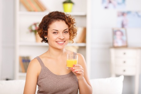 tomando jugo: Portrait of pleasant attractive vivacious girl holding glass and drinking juice while having breakfast Foto de archivo