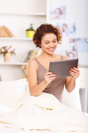upbeat: Pleasant upbeat young  attractive girl sitting in bed and holding laptop while evincing joy
